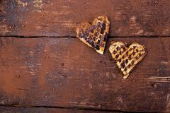 Two belgian heart shaped waffle with chocolate on wooden background. Flat lay. Copy space Royalty Free Stock Image