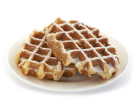 Two belgian waffles served on a plate. Two fresh and tasty belgian sugar waffles served on a plate, sprinkled with nice sweet powder sugar Royalty Free Stock Photos
