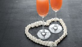 Two bellini cocktails inside of meringue heart Stock Images