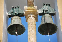 Two bells on the church tower in Corfu, Greece. Two green big bells on the tower of the old church located on the Greek island of Corfu. Big bells to announce Stock Photos