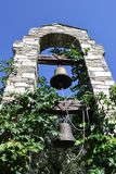 Two bells hanging on wooden beams in the stone arch among green plants Stock Photography
