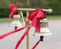 Two bells with red ribbon on the stand for the groom and  bride Stock Images