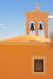 Two bells. A small church painted orange Royalty Free Stock Images