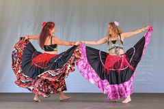 Two belly dancers in long colorful skirts stock image