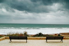 Two bench. In a stormy day facing the sea Royalty Free Stock Images