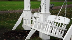 Two bench swings swinging stock video footage