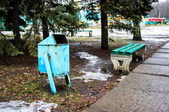 Two benches and bin in the park. Two benches and bin in the park at the firs. Early spring, the snow and ice on the grass Royalty Free Stock Image