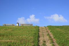 Two benches and a bin to picnic or rest at the sea dyke in summer. Two benches and a bin next to the stairway at the sea dyke in summer with green grass and a Stock Image