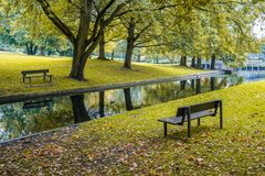 Two benches in a park with a small stream Royalty Free Stock Photography
