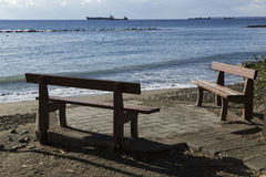 Two benches on the shore of the sea and ships in the distance. Royalty Free Stock Image