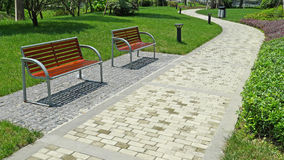 Two benches with stone path Royalty Free Stock Photography