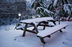 Snow covered picnic table and benches during winter. Two benches, a table and the surface is covered with snow during winter. Near the benches there are pine Stock Photo