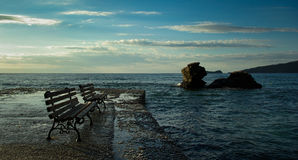 Two benches and two rocks in the sea Stock Image