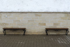 Two benches at the wall. Royalty Free Stock Image
