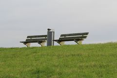 Two benches and a waste bin at the green sea dike to relax and watch the ships. Two benches and a waste bin at the green sea dike to chill and have a wonderful Royalty Free Stock Images