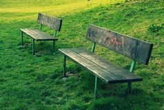 Two benches. Two wooden benches in park. One of them is tagged by graffitty symbol Stock Images