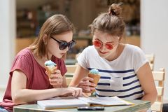 Two best female companions with serious expressions, being focused in menu, choose what to eat in cafeteria, enjoy ice cream, dres. Sed in casual t shirt and royalty free stock images