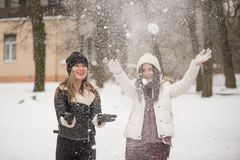 Two best female friends play with snow. Winter outdoor activities, positive emotions, joy and happiness royalty free stock photo