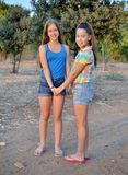 Two best friend girls holding hands. Best Friends Forever - two 12 year old teenage girls  holding hands at sunset Stock Image