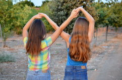 Two best friend girls making a forever sign. Best Friends Forever - two 12 year old teenage girls  holding hands in an infinity forever sign to signify BFF Royalty Free Stock Image