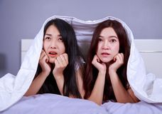 Best friend woman on bed watching a tv with shocked expression o. Two best friend women on bed watching a tv with shocked expression on face Stock Photos