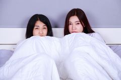 Best friend woman on bed watching a tv with shocked expression o. Two best friend women on bed watching a tv with shocked expression on face Royalty Free Stock Image
