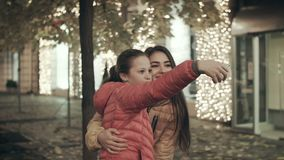 Two best friends with cell phone camera taking photos under autumn fall in night. Two best friends with cell phone camera taking photos under autumn fall in stock footage