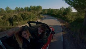 Traveling in convertible car for life. Two best friends or girlfriends make selfie video or self portrait photo on stick action camera, while stand up inside stock video