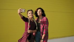 Two best friends girls having fun and making selfie standing by the yellow wall. Two hipster girls taking selfie photos. With smart phone and smiling stock video footage