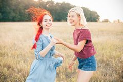 Two best friends spend time outdoors. Two best friends having fun on the field under sunlight stock photos