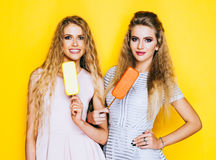 Two best friends having ice cream together indoor on yellow background. Close up of young women eating ice cream and Royalty Free Stock Images
