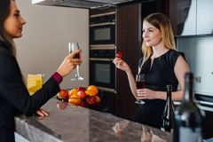 Two best friends having a little house-warming party by drinking red wine standing in the kitchen Stock Photos