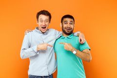 Two best friends hugging, pointing finger each other and looking. At camera with shocked face. Studio shot on orange background royalty free stock images