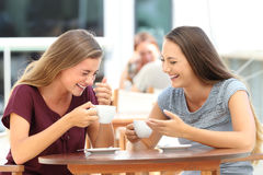 Best friends laughing loud during a conversation in a bar. Two best friends laughing loud during a conversation sitting in a restaurant Royalty Free Stock Image