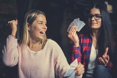 Two best friends playing game cards at home. stock photography