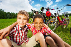 Two best friends sit on grass and hug with arms. With bikes standing behind them Stock Images