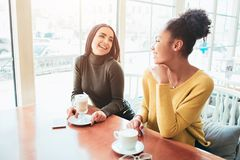 Two best friends are sitting in cafe and spending good time together. Girls are drinking some latte and enjoying their royalty free stock images