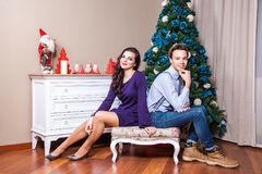 Two best friends looking at camera with toothy smile and posing to christmas photo. Two best friends sitting on a chair, looking at camera with toothy smile and Royalty Free Stock Photos
