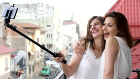 Two best friends smiling and laughing while taking a selfie. Photo with a selfie stick on the balcony. Slow motion stock footage