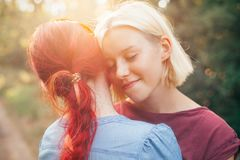 Two best friends spend time in forest. Two young females hugging in forest. Best friends. Close up stock image