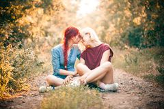 Two best friends spend time in forest. Two young women sitting on the road in forest. Best friends stock photo