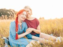 Two best friends spend time outdoors. Two girls sitting on the grass and laughing. Best friends royalty free stock photo