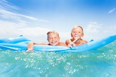Two best friends swimming on matrass and splashing Royalty Free Stock Photo