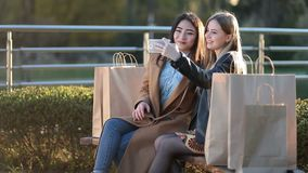 Two best friends taking selfie with smartphone. Young happy teenage girls using their phones doing selfie after shopping at sunset in the park. Two attractive stock video