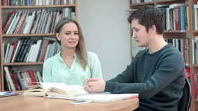 Two best friends talking and laughing over good books in library. Professional shot in 4K resolution. 075. You can use it e.g. in your commercial video stock video footage