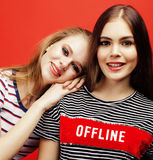 Two best friends teenage girls together having fun, posing emotional on red background, besties happy smiling, lifestyle Royalty Free Stock Images