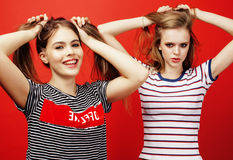 Two best friends teenage girls together having fun, posing emotional on red background, besties happy smiling, lifestyle Royalty Free Stock Photos