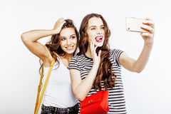 Two best friends teenage girls together having fun, posing emotional on white background, besties happy smiling, making Royalty Free Stock Photo