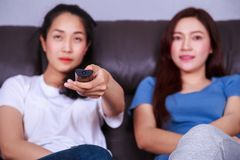 Two best friends watching tv with remote on sofa at home. Two best friends watching tv with remote on sofa in living room at home Stock Photo