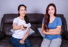 Two best friends watching tv with remote on sofa at home. Two best friends watching tv with remote on sofa in living room at home Stock Images